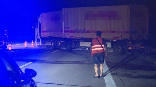 Ein Lastwagen steht quer auf einer Autobahn.