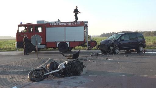 Ein zerstörtes Motorrad liegt auf einer Landstraße, dahinter ein zerstörter PKW und ein Feuerwehrauto.