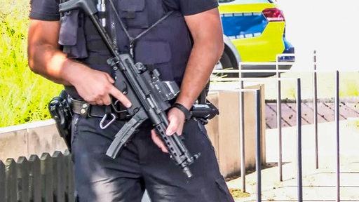 Ein Polizist mit einer Maschinenpistole | Nord-West-Media TV/