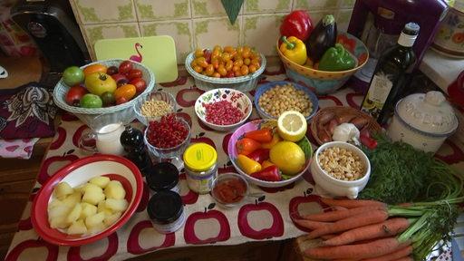 Ein Tisch, auf dem einige Schalen mit Obst, Gemüse und Hülsenfrüchten zu sehen sind.