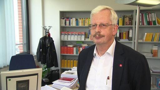 Onno Dannenberg, stehend in seinem Büro.