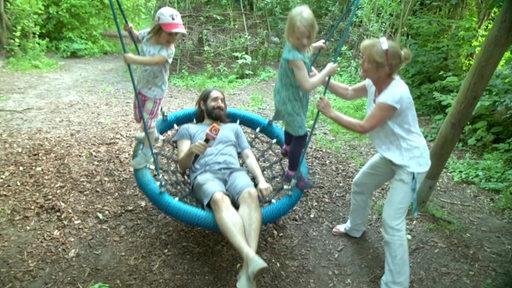 Freddy Radeke schaukelt mit Kindern auf einem Natur-Spielplatz.