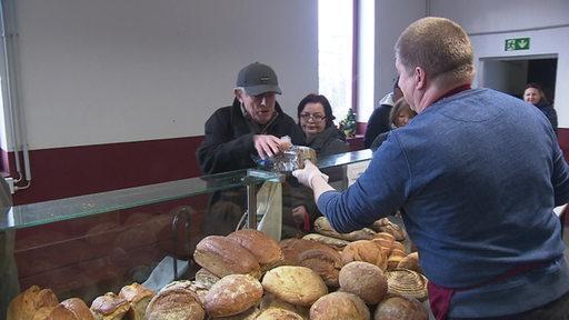 Mitarbeiter der Tafel in Hemelingen händigen Bedürftigen über den Tresen Brot aus.