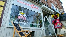 """Auf einem Schaufenster steht """"Pinguins Café"""" und """"Springflut"""", davor steht ein Ligestuhl, seitlich stehen zwei Maskottchen."""