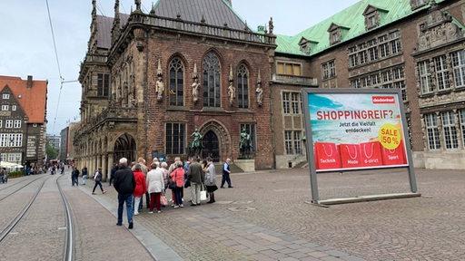 Ein Plakataufsteller mit Werbung für das Einkaufshaus Dodenhof außerhalb der Stadt steht in der Innenstadt von Bremen