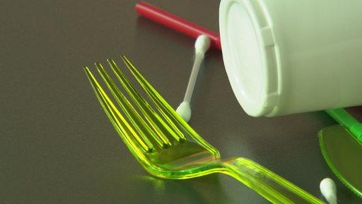 Eine Nahaufnahme einer Plastikgabel, im Hintergrund weitere Gegenstände aus Plastik.