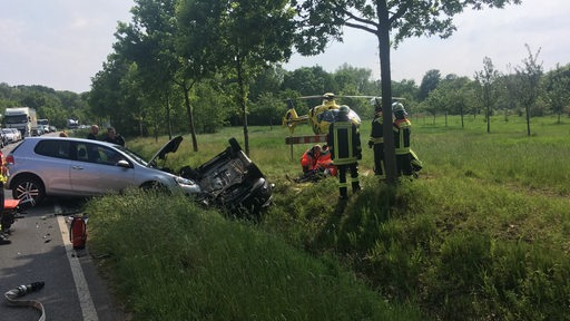 Zwei Autos liegen in einem Graben, Feuerwehrmänner und Sanitäter helfen