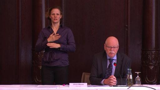 Der bremer Innensenator Ulrich Mäurer bei einer Pressekonferenz im Bremer Rathaus. Hinter ihm steht eine Gebärdendolmetscherin.