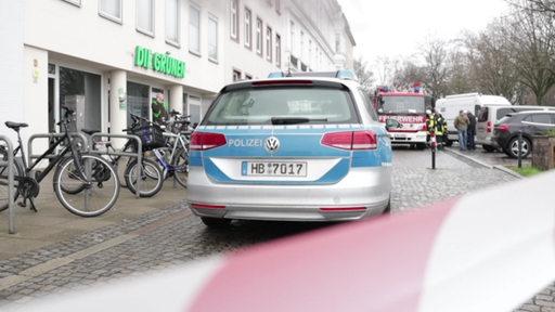 Ein Polizeiwagen hinter eine Absperrung vor dem Büro der Partei