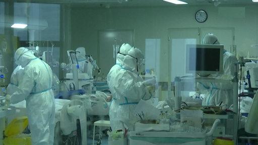 Medizinisches Personal in einer Quarantäne-Station in Schutzanzügen