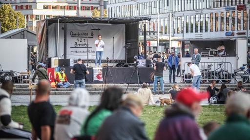 Sprecher auf einer Bühne während einer Querdenken-Demonstration in Bremen