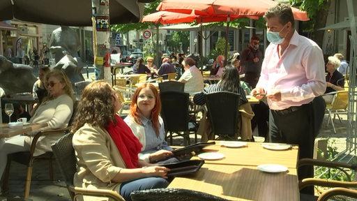 Zwei Frauen sitzen an einem Tisch und sprechen mit dem Kellner, der einen Mundschutz trägt | Radio Bremen/