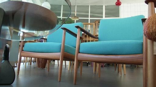 Zwei Retro-Sessel mit türkisem Bezug.