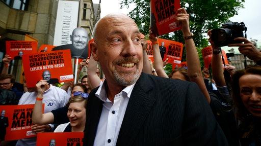 Carsten Meyer-Heder lacht in die Kamera, im Hintergrund sind einige Anhänger zu sehen