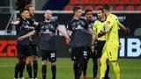 Werder-Spieler stehen mit ratlosen Miene und ausgestreckten Armen vor dem Schiedsrichter und beschweren sich.
