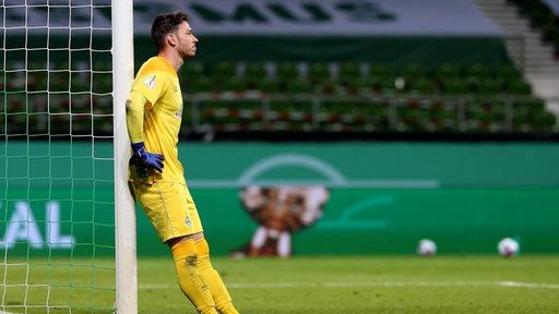 Werder-Torwart Jiri Pavlenka lehnt frustriert am Pfosten und starrt ins Leere.