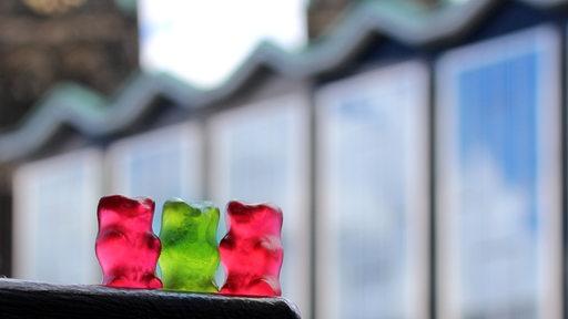 Ein roten, ein grünes und ein rotes Gummibärchen vor dem Haus der Bürgerschaft.