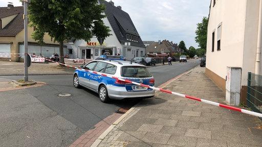 Ein Polizeiwagen steht vor einem abgesperrten Tatort.