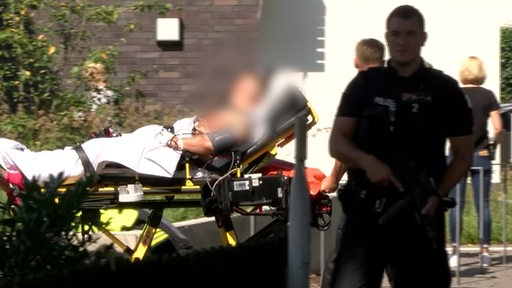 Ein angeschossener Mann wird auf einer Tragelieger von Krankenhelfer geschoben.