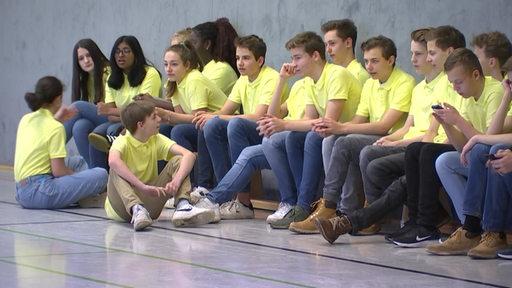 Eine Schulklasse in gelben T-Shirts auf einer Bank in einer Sporthalle sitzend.