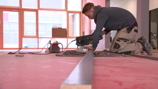 Ein Handwerker bei der Arbeit in einer Bremer Schule