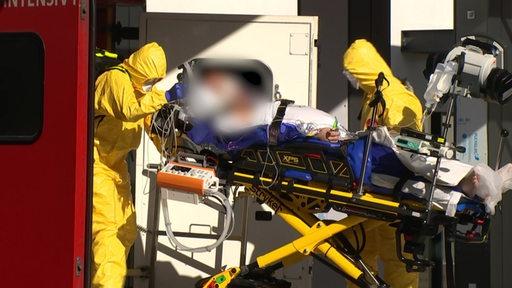 Zwei Menschen mit Schutzkleidung und Gesichtsmasken transportieren einen Patienten auf einer Liege aus einem Krankenwagen.