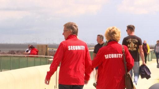 Zwei Personen, die rote Jacken mit der Aufschrift 'Security' darauf tragen.