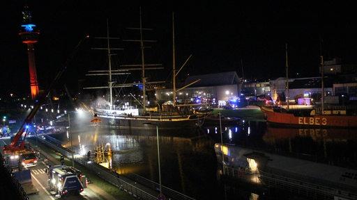 Ein Schiff und Feuerwehrfahrzeuge