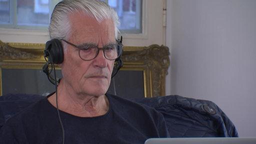 Der Schauspieler Sky du Mont, der sich etwas mit Kopfhörern auf den Ohren auf einem Laptop anschaut.