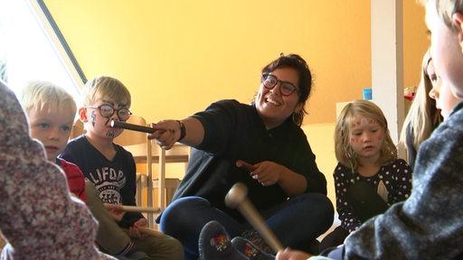 Eine spanische Erzieherin musiziert mit Kindern, welche in einem Kreis sitzen.