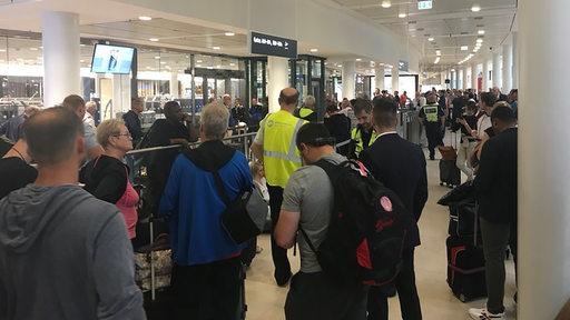 Menschen stehen am Bremer Flughafen vor einer Sicherheitstür.