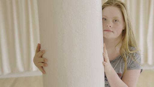Ein Mädchen steht hinter einer Säule.