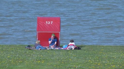 Hinter einem Strandkorm liegen drei Personen auf einer grünen Wiese, hinter ihnen das Meer.