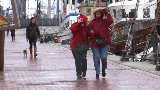 Spaziergänger an der Hafenpromenade in Bremerhaven während des Sturms Victoria