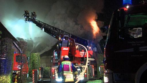 Ein Haus steht in Flammen und Feuerwehrmänner bemühen sich, es zu löschen.