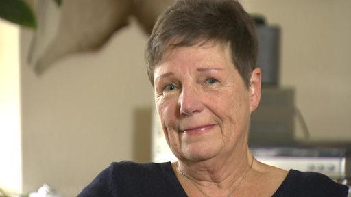 Eine ältere Frau mit Kurzhaarschnitt lächelt in die Kamera.