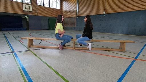 Zwei Schülerinnen sitzen sich auf einer Bank in einer Turnhalle gegenüber