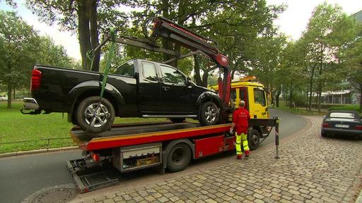 An Abschleppwagen hebt ein Auto hoch.