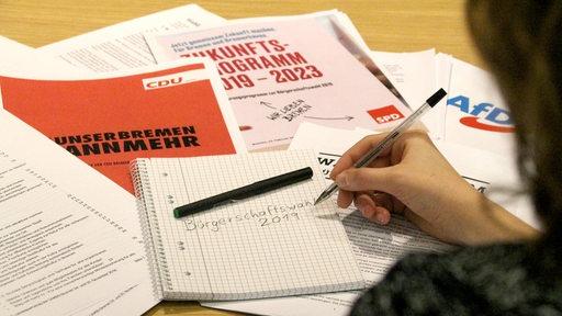 Verschiedene Wahlprogramme liegen auf einem Schreibtisch verteilt.