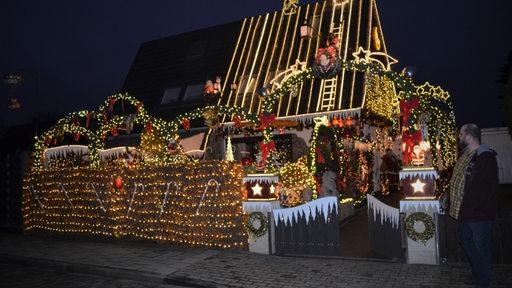 Mann steht vor weihnachtliche beleuchteter Doppelhaushälfte in Delmenhorst.