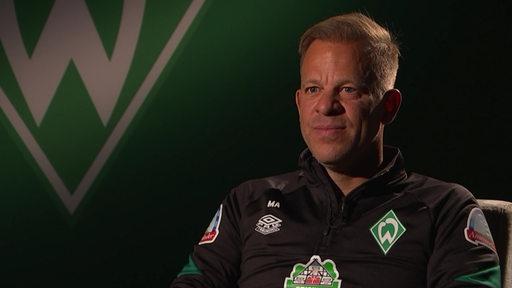 Markus Anfang sitzt in einem Sessel während des Interviews. Hinter ihm ist das Werder-Logo zu sehen.
