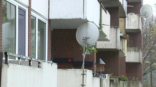 Balkone mit Satellitenschüsseln an einem Gebäude.